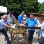 Die Wettkämpfe beginnen: Baumstammsägen Zuerst Team Engel